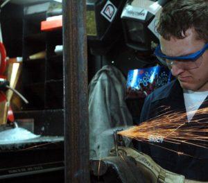 Der Mann arbeitet konzentriert mit einem 150mm Exzenterschleifer. Vielleicht ist sie ja von Bosch, das ist auf dem Bild aber leider nicht zu erkennen.